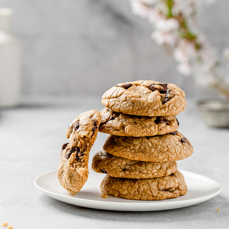close up of chocolate chip cookies in a stack on a plate