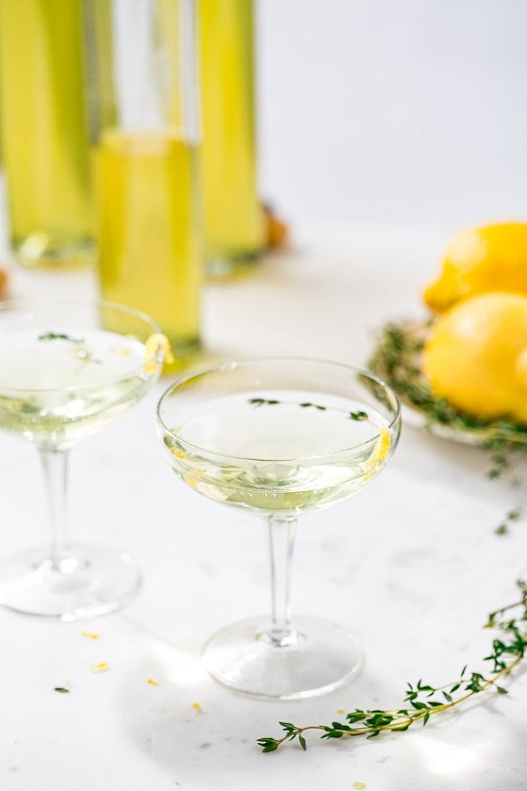 Lemon Thyme cocktail in coupe glasses with limoncello bottles in the background