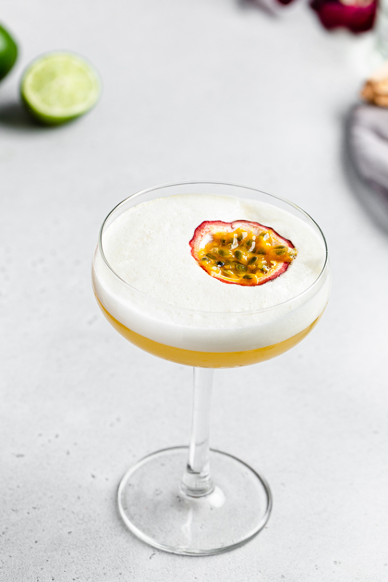 top view of passionfruit mango sour with the passionfruit floating in egg white foam