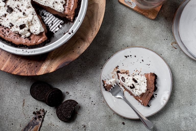 Chocolate cream pie slice on a plate next to the rest of the pie