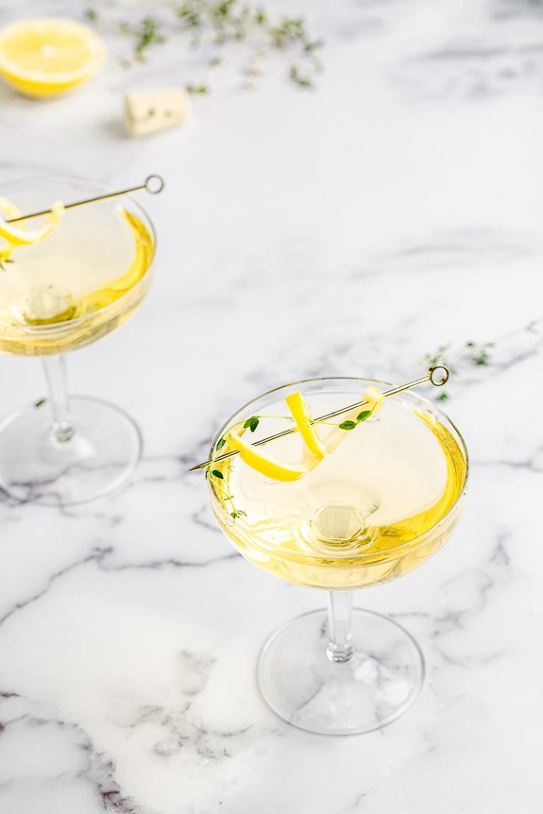 Lemon Thyme cocktail in coupe glasses with limoncello and lemon twist garnish